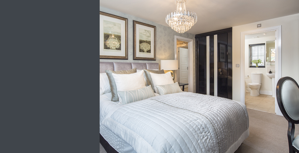 Bedroom with pale blue bedsheets and a shimmering chandelier