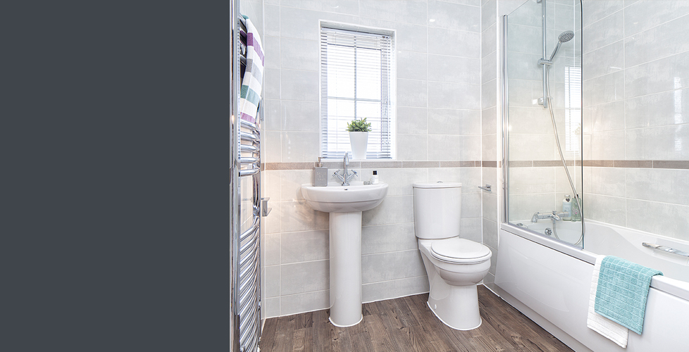 A bathroom with combined shower and bath, with light grey tiling