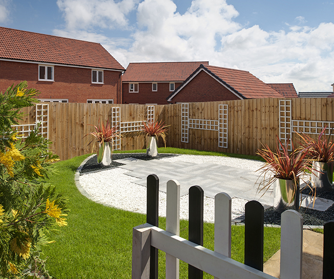 a Barratt home surrounded by fencing, and the focal point of the garden being an area of paving