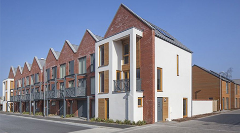 A row of houses which a rich red brickwork and modern design features