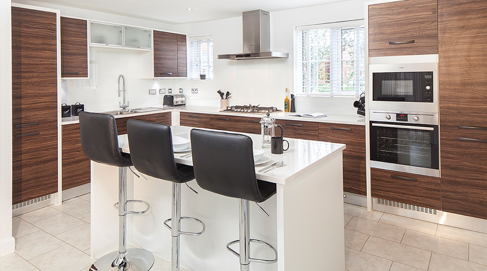 A kitchen with central breakfast island, and customised units and surfaces