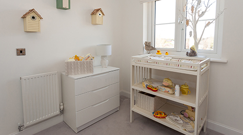 a nursery with a fresh white theme and birdhouses decorating the walls