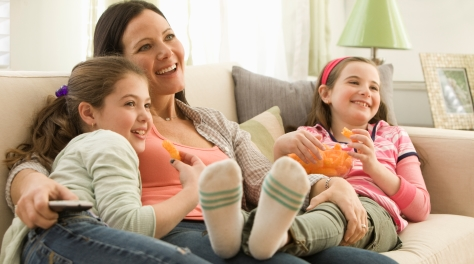 Mother and daughters watching television