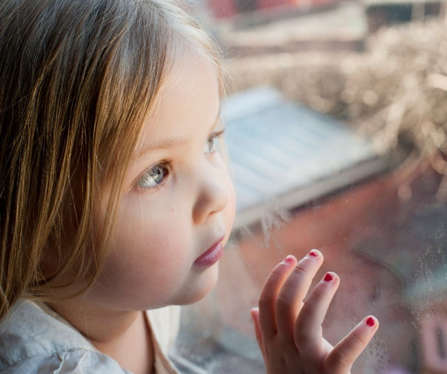 a girl stares out of a double glazed window