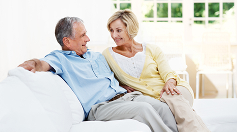 an elderly couple smile at each other as they smile at each other on the sofa in their Barratt home