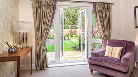 a living room furnished with gold coloured curtains and a plush purple armchair